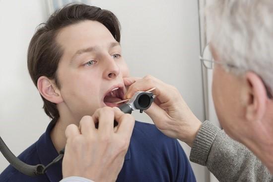 Осмотр пациента с больным горлом врачом-отолорингологом